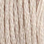 A close-up view of embroidery thread skeins, held taught vertically. The shade is a very light, pale cream, like almond milk
