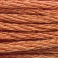 A close-up view of embroidery thread skeins, held taught horizontally. The shade is a medium dark brick orange, like cinnamon but not as red