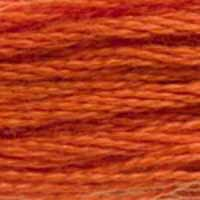 A close-up view of embroidery thread skeins, held taught horizontally. The shade is a medium pumpkin orange, like a freshly carved jack-o-lantern