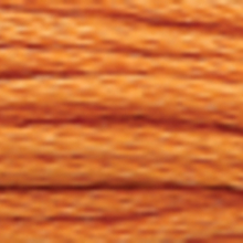 "A close-up view of embroidery thread skeins, held taught horizontally. The shade is a dark honey colour in six strand cotton floss, like a ""Circus Peanut"" candy."
