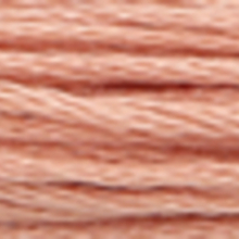 A close-up view of embroidery thread skeins, held taught horizontally. The shade is a light tawny pink colour in six strand cotton floss, like tea rose petals.