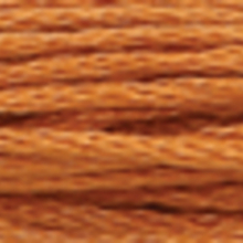 A close-up view of embroidery thread skeins, held taught horizontally. The shade is a medium ruddy brown colour in six strand cotton floss, like cinnamon french toast.