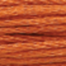 A close-up view of embroidery thread skeins, held taught horizontally. The shade is a medium light toasted brown colour in six strand cotton floss, like a pumpkin pie.