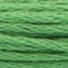 A close-up view of embroidery thread skeins, held taught horizontally. The shade is a medium light apple green colour in six strand cotton floss, like crabgrass
