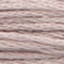 A close-up view of embroidery thread skeins, held taught horizontally. The shade is a pale grayish purple colour in six strand cotton floss, like a tin camping dish