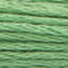 A close-up view of embroidery thread skeins, held taught horizontally. The shade is a light forest green colour in six strand cotton floss, like minty toothpaste