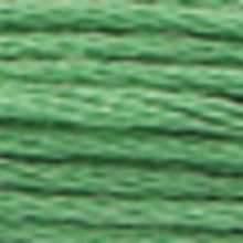 A close-up view of embroidery thread skeins, held taught horizontally. The shade is a medium light forest green colour in six strand cotton floss, like mint ice cream.