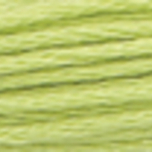 A close-up view of embroidery thread skeins, held taught horizontally. The shade is a pale yellow green colour in six strand cotton floss, like hops ripe for beer